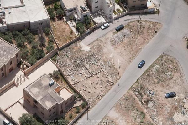 Figure 2: This 2013 aerial photograph shows a road over a section of an exposed excavation of the remains of a church in Ma'in, Jordan (APAAME_20130414_MND-0484 Ma'in).