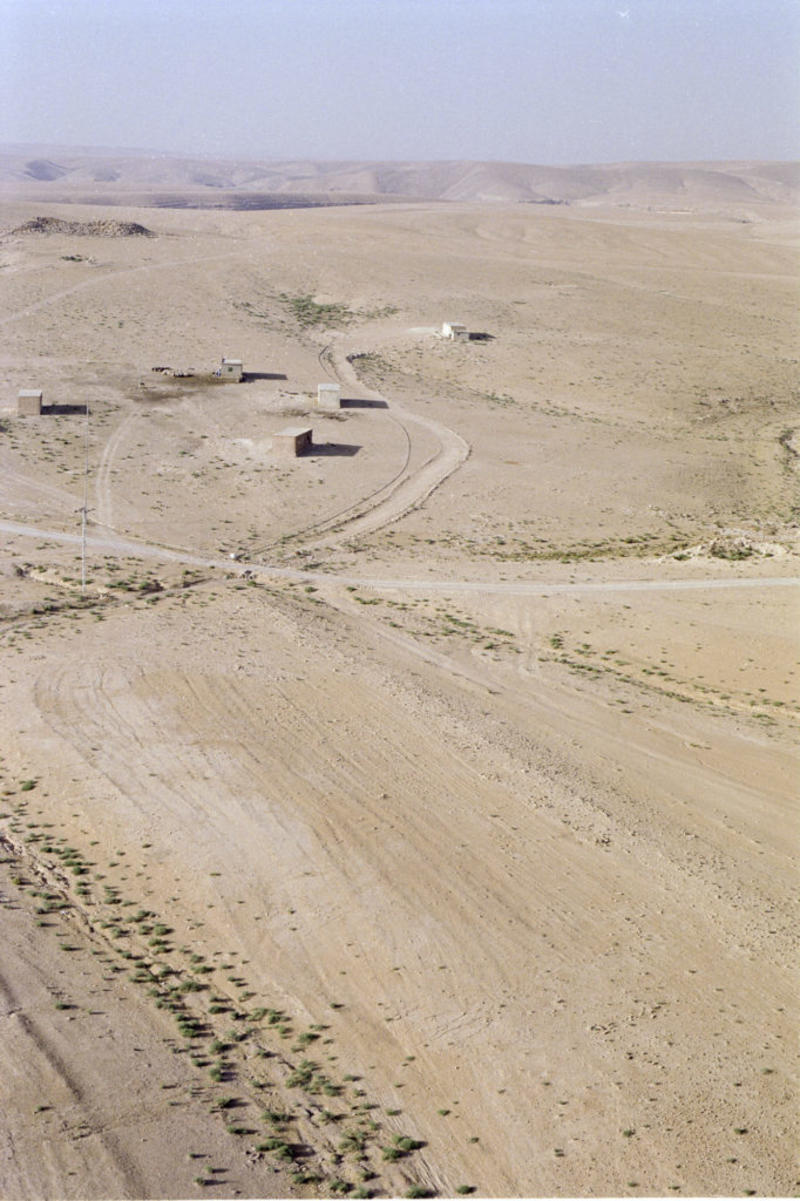 Aerial view of Qasr eth-Thuraiya (background) with the Roman road visible in the ploughed field (foreground). Photograph: Robert Bewley. APAAME_20040532_RHB-0174.